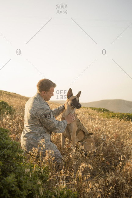 Airman training his Military Working Dog on hillside