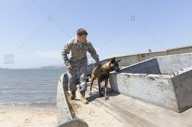 Serviceman training with his Military Working Dog on boat