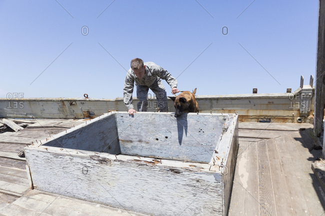 Military Working Dog and his handler investigate a boat hatch