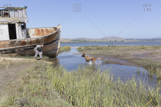 Soldier working with his Military Service Dog near old boat
