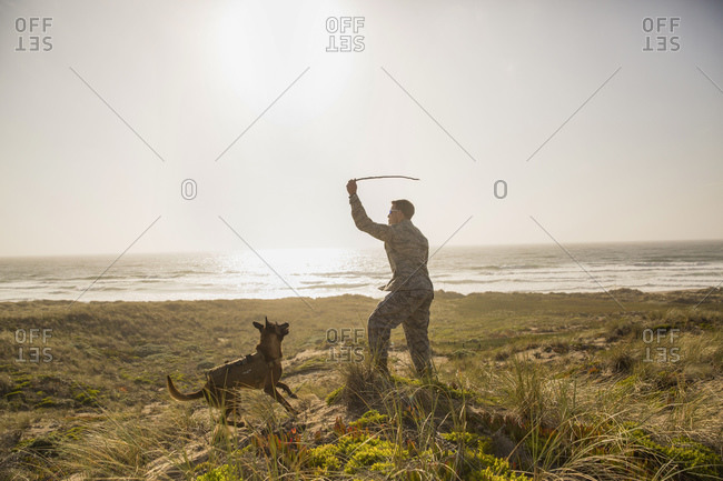 Soldier playing fetch with his Military Service Dog