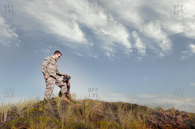 Portrait of soldier petting his Military Service Dog on hillside