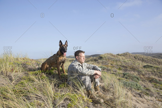 Portrait of soldier and his service dog sitting on a hillside