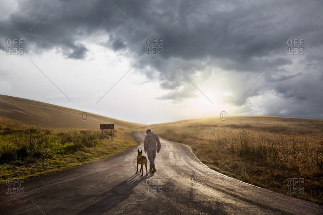Soldier and his service dog walking down road at end of day