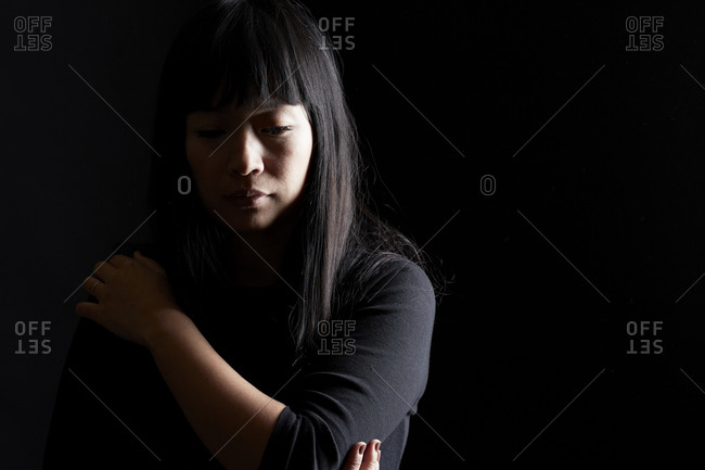 Sad young woman hugging herself