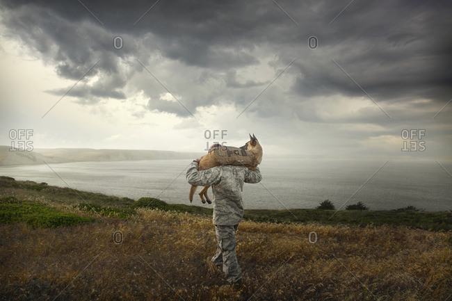 Soldier carrying his service dog on his shoulders