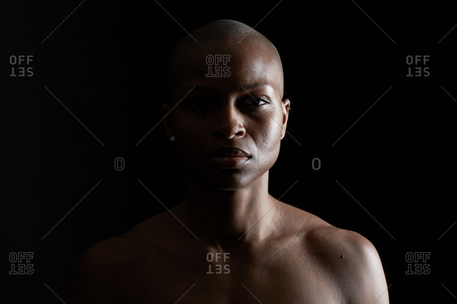 Strong young woman with a shaved head staring ahead