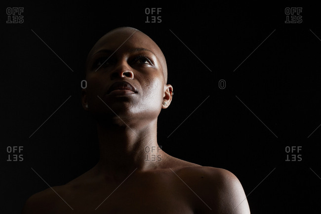 Strong young woman with a shaved head staring above her