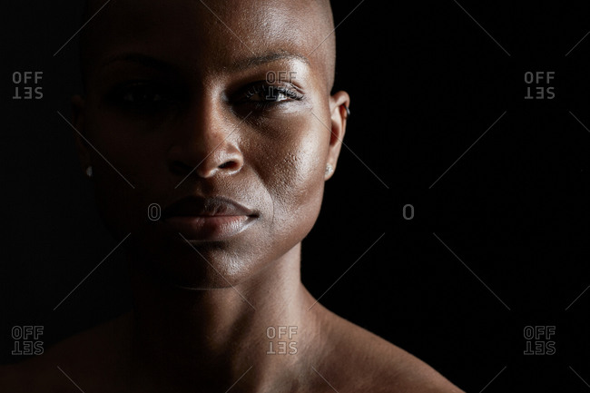 Strong young woman with a shaved head staring at the camera