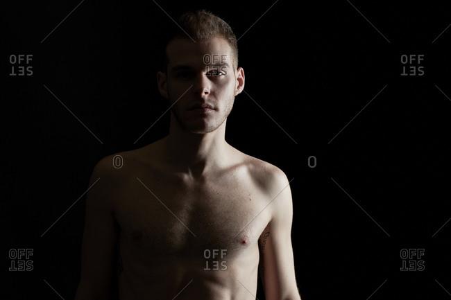 Shirtless young man staring at the camera