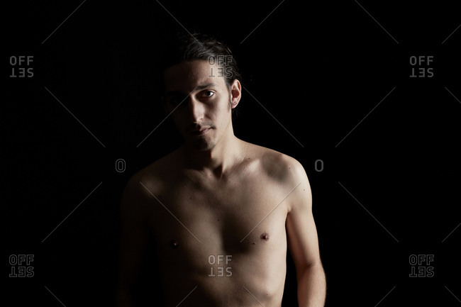 Young shirtless man with brown hair looking at camera
