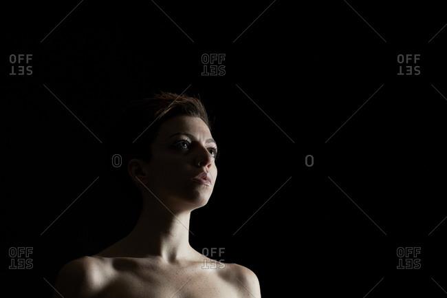 Shirtless young woman gazing ahead