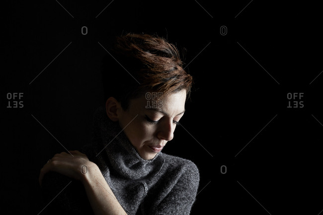 Young woman in a gray sweater hugging herself