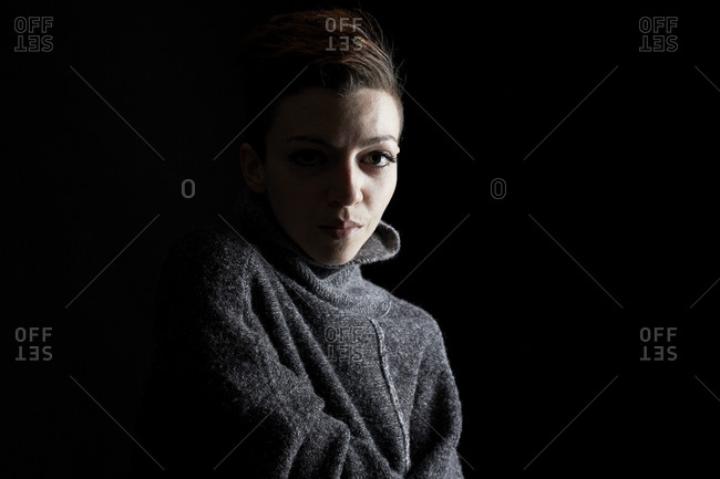 Young woman in a gray sweater looking at the camera