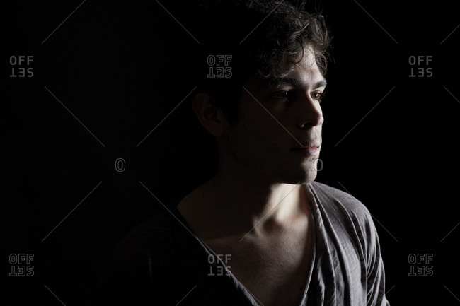 Man in a gray t-shirt lost in thought