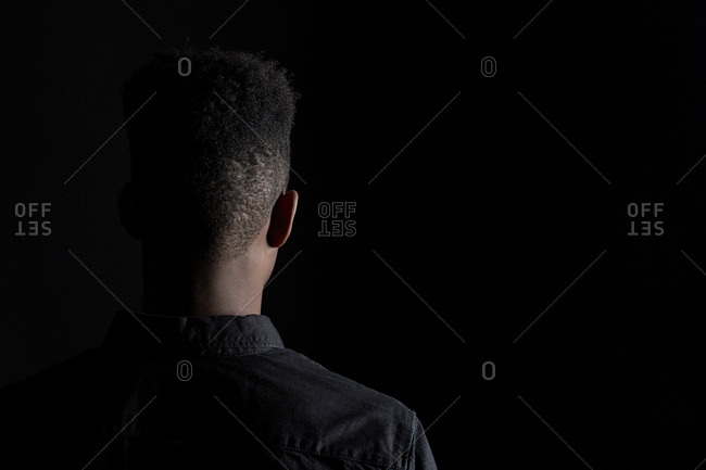 Back of a young man in a denim shirt