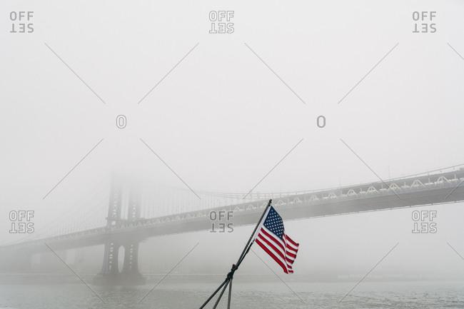 American flag fluttering in the fog near the Manhattan Bridge