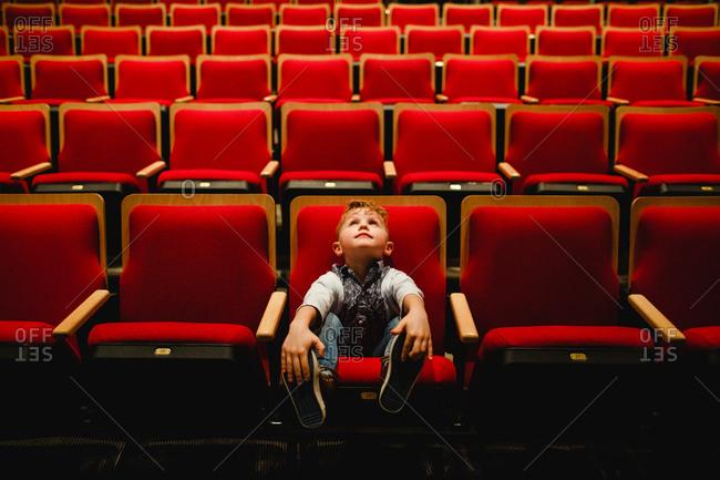 Little boy sitting in a row of empty theatre seats