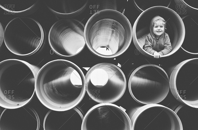 Little boy in stack of construction tubes