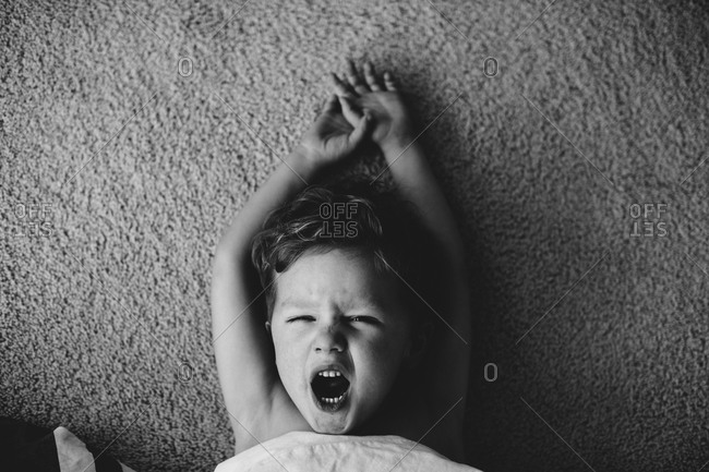 Little boy on a carpet yawning and stretching