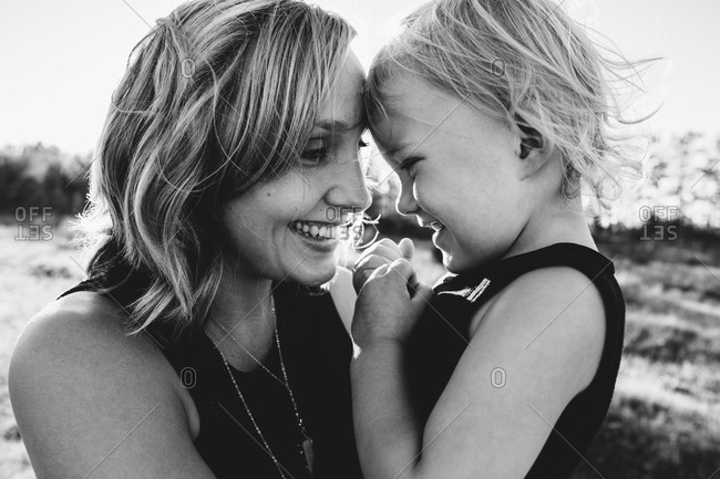 Woman and daughter touching foreheads and smiling