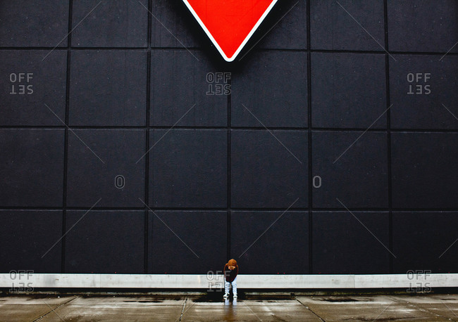 Child by wall of modern building