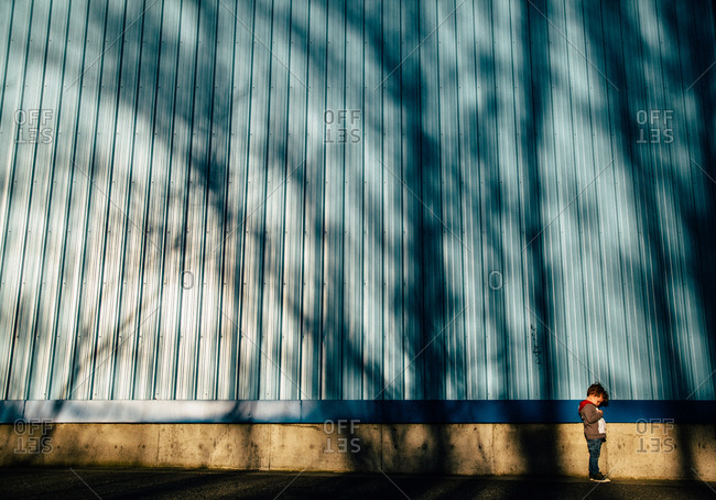 Boy in tree shadows by building