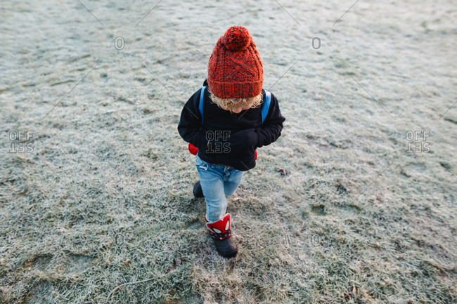 Little boy with a backpack walking across a frosty yard