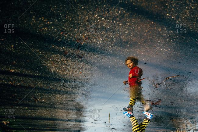 Reflection of a little boy walking on a wet road