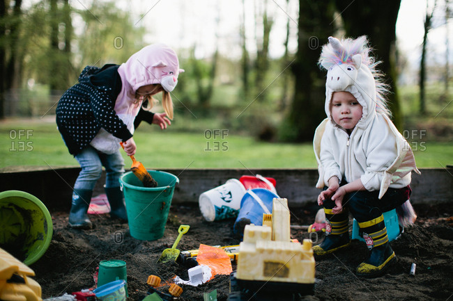Kids in a unicorn and cat costume playing in a sandbox