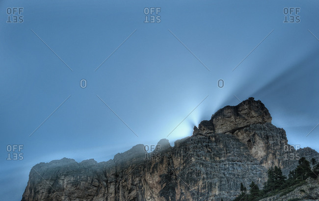 Sun light beams behind cliff