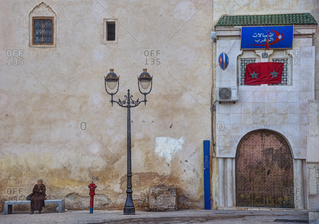 Fes, Morocco - December 8, 2015: Woman on a bench in the Rcif square
