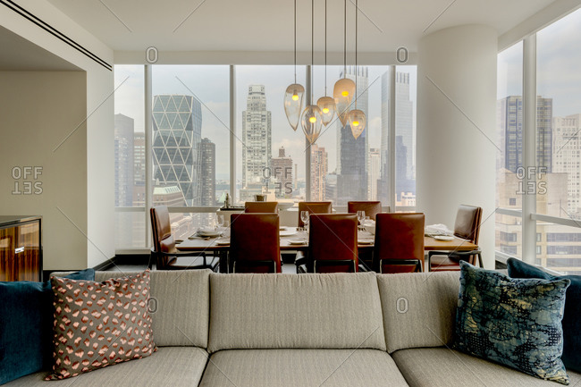 New York, NY - July 27, 2015: Living room and dining room in luxury high-rise apartment