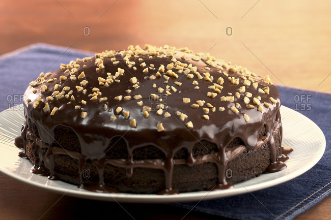 Chocolate layer cake with dripping frosting and nuts