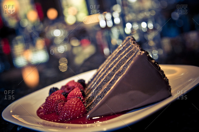 Slice of chocolate layer cake with berry sauce