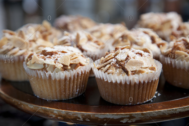 Muffins topped with slivered almonds and powdered sugar