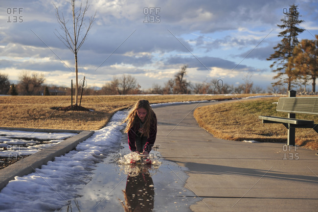 Girl skateboarding through a puddle of melting snow