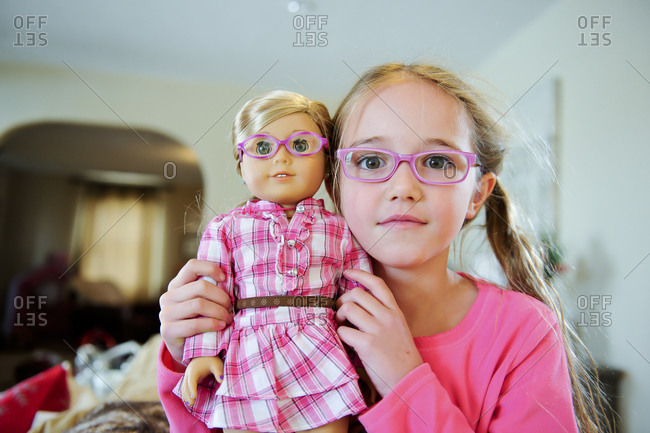 Girl holding doll that looks like her