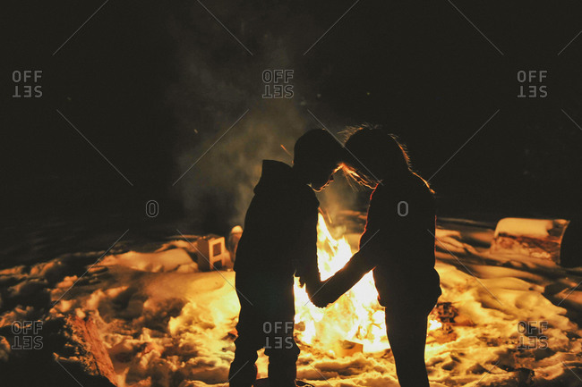 Silhouette of children holding hands by a winter bonfire