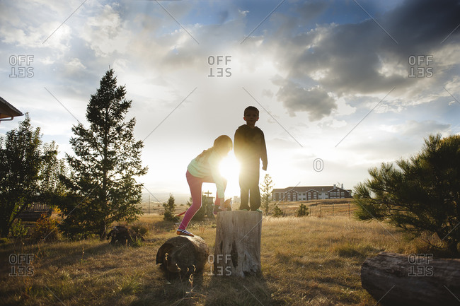 Silhouette of children climbing on a tree stump