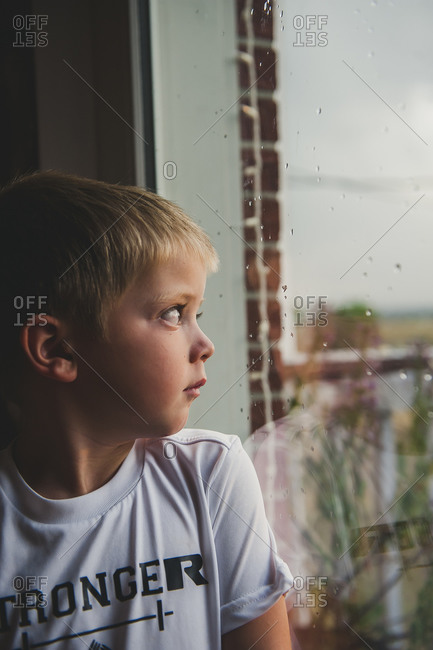 Boy looking out window on a rainy day