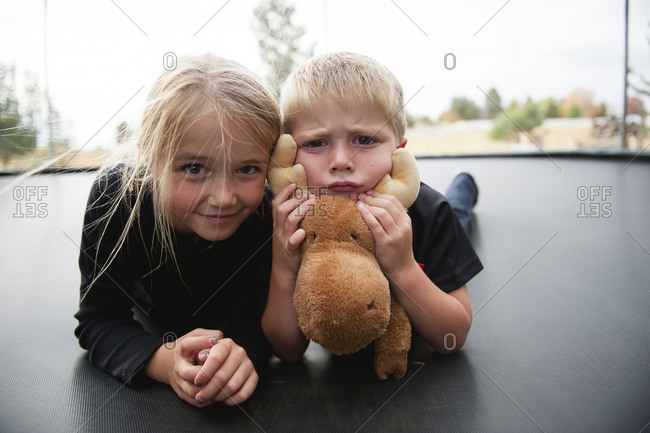 Children playing on a trampoline with a stuffed moose