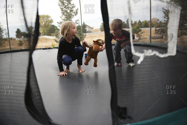 Children playing with a stuffed moose on a trampoline