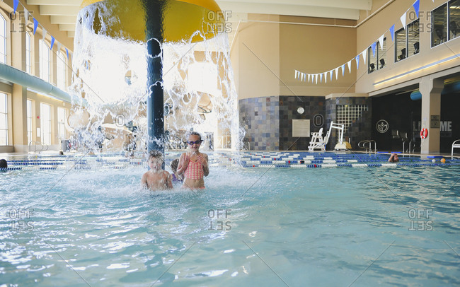 Siblings being splashed with water at an indoor pool