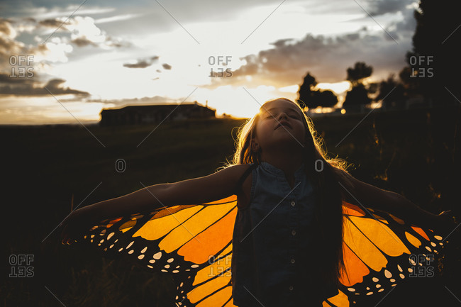 Girl wearing monarch butterfly wings at sunset