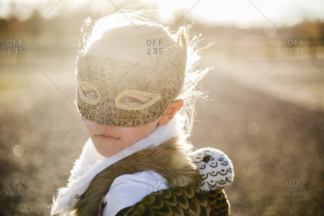 Girl wearing feathered mask