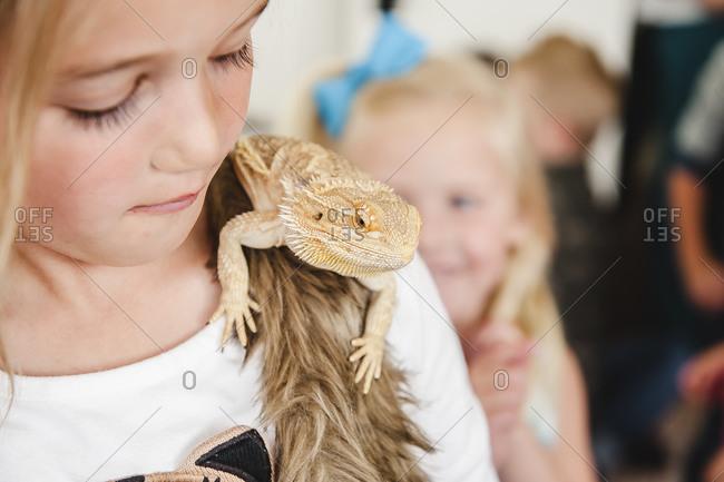 Little girl holding lizard on her shoulder