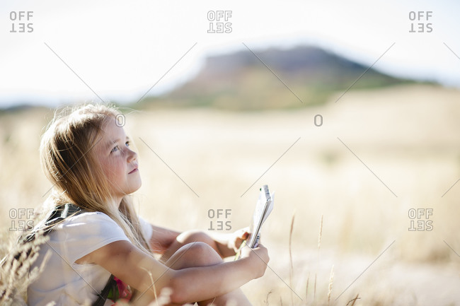 Girl sitting in a field with a pen and notebook