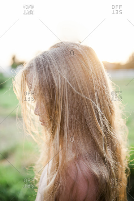 Portrait of a little blonde girl with hair covering her face