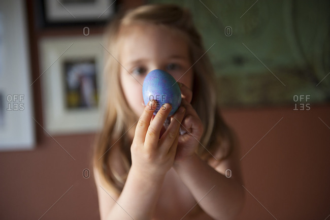 Portrait of a little girl holding a blue Easter egg